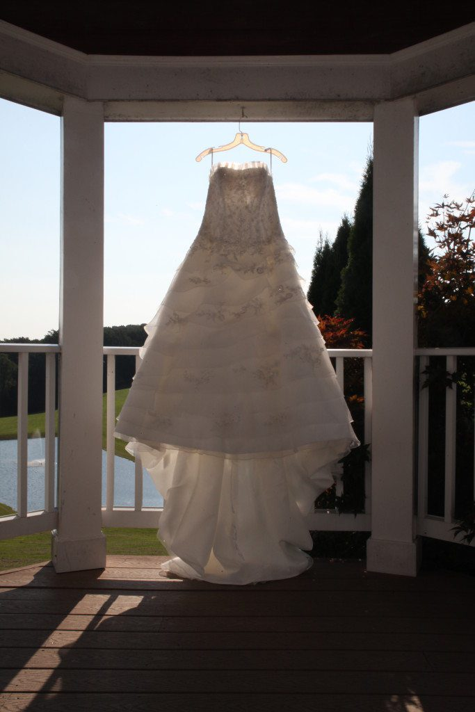 The wedding dress hangs in the inside wedding area and is highlighted by the sun. This area is used as an alternative ceremony location if weather prohibits an outside wedding ceremony.