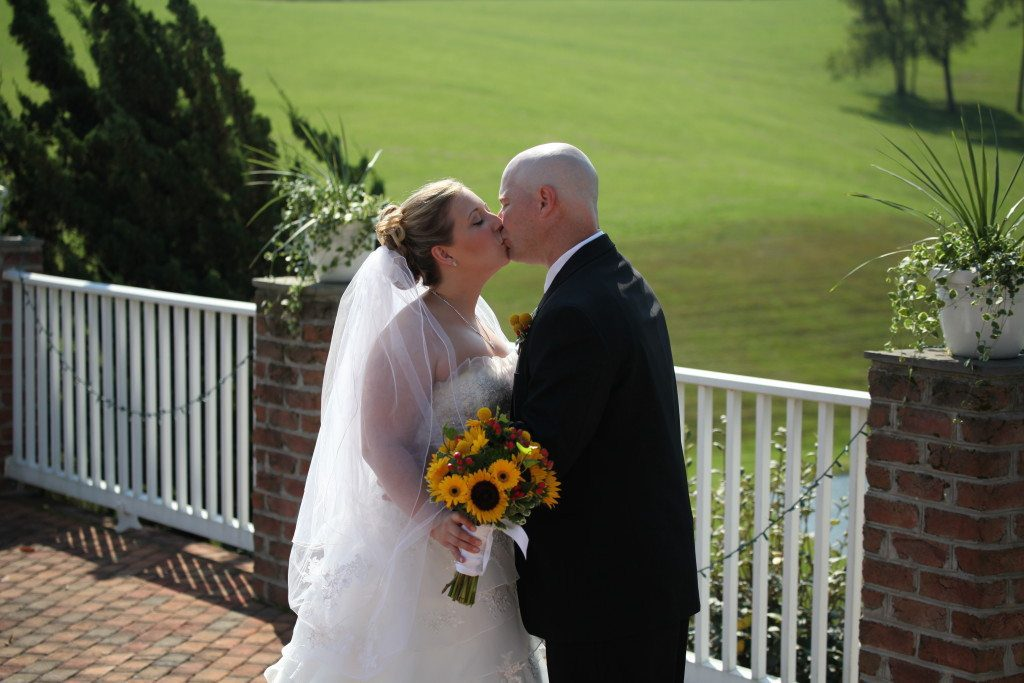 Bride and groom kiss on the patio of Morningside Inn after their summer outdoor wedding ceremony.