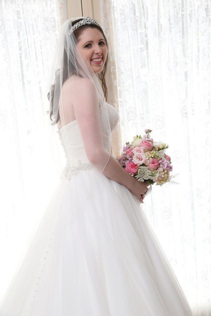 Bride stands by door in bride's room before outdoor wedding ceremony