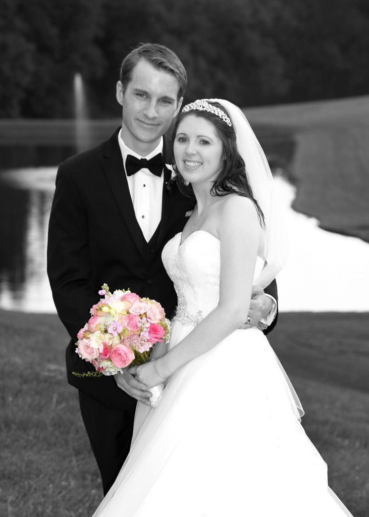 Bride and groom by pond black and white with color flowers