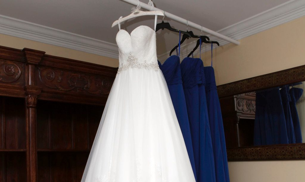 Bride's wedding dress hangs in the brides room at Morningside Inn wedding ceremony site