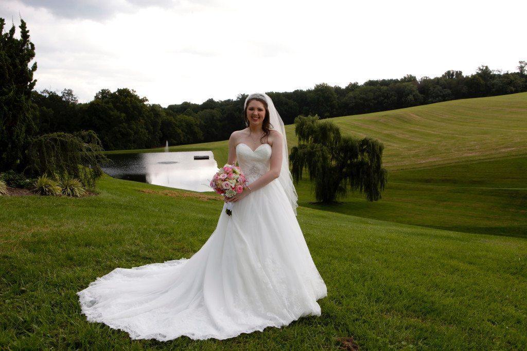 Bride by wedding venue with pond