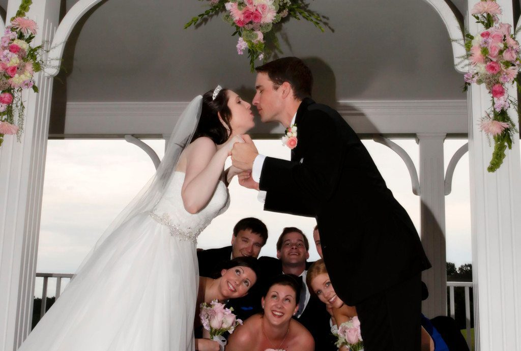 Bride and groom kiss on pavilion with wedding party watching