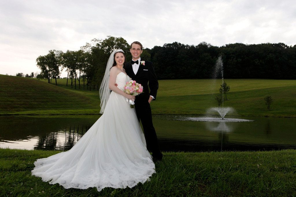Bride and groom after outdoor wedding ceremony stand by pond at Morningside Inn
