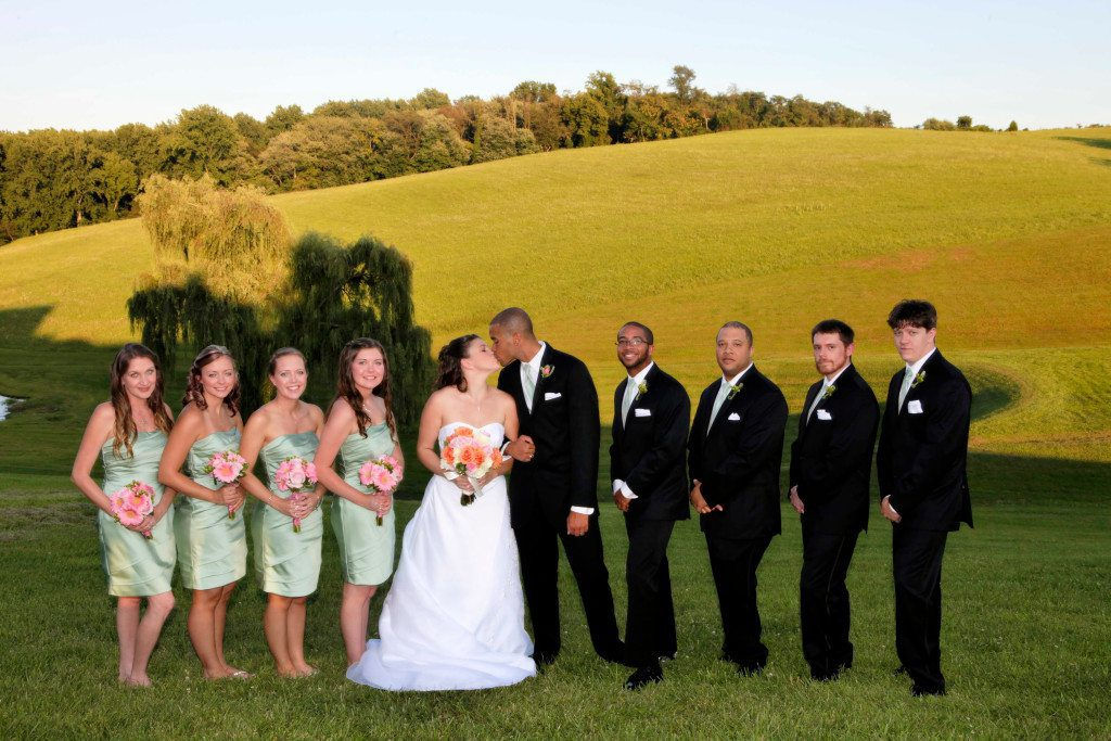 Wedding party on lawn by pond and willow tree
