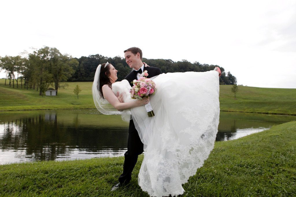 Groom carries bride by pond after wedding at Morningside Inn