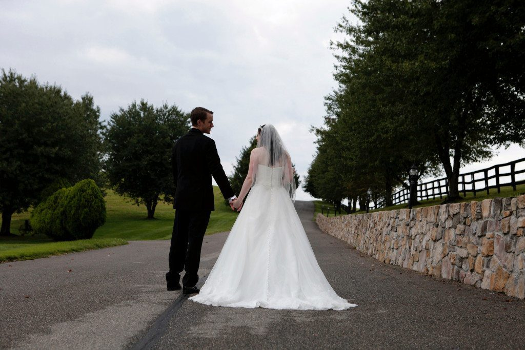 Bride and groom walk away from camera up driveway