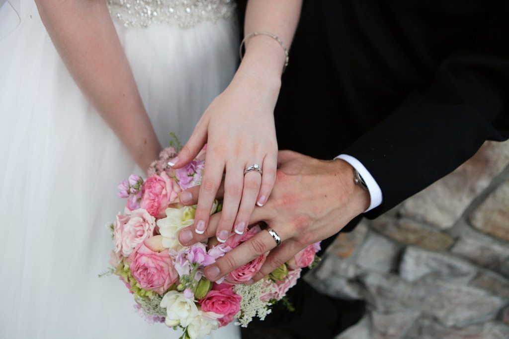 Bride and groom show rings over summer wedding flowers