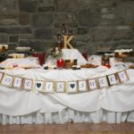 "creative wedding favor idea of decorated table of cookies and homemade treats. banner is attached to front of table displaying ""love is sweet"""