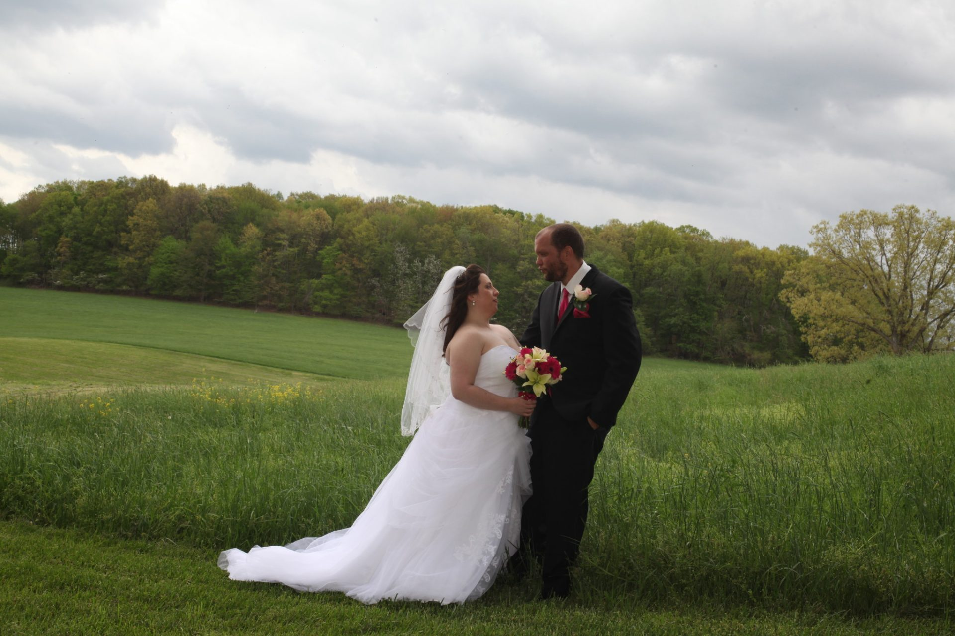 Outside wedding at Morningside Inn, bride and groom pose with rolling hills as backdrop