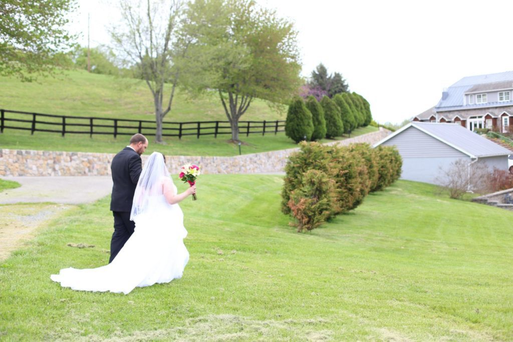 Outside wedding at Morningside Inn, bride and groom pose with rolling hills, wooden fence and country inn as backdrop