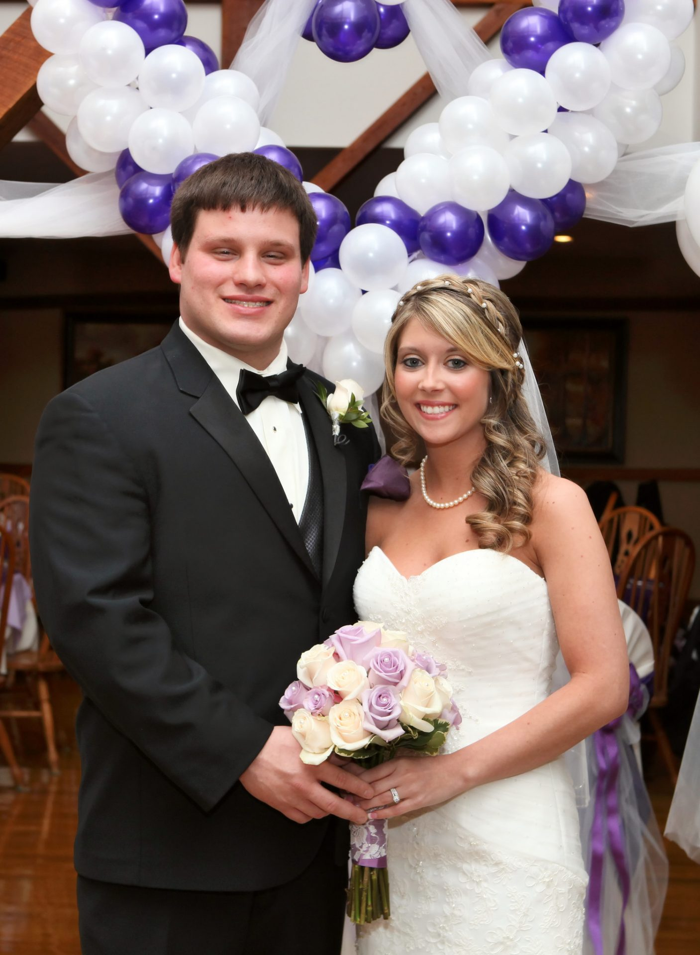 Bride and groom pose in front of white and lavander ballons