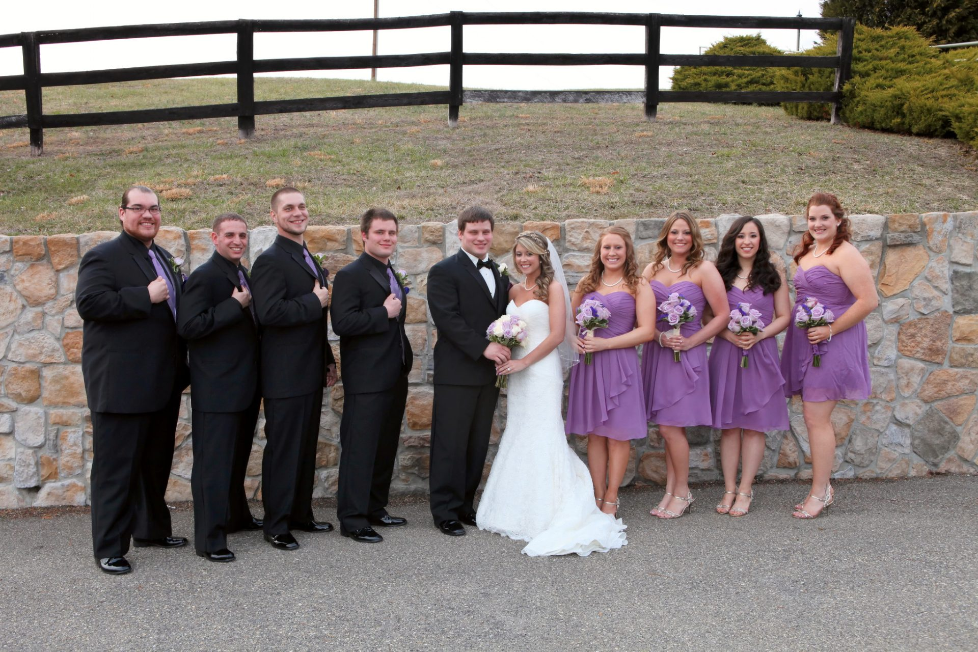 Wedding party pose in front of stone wall