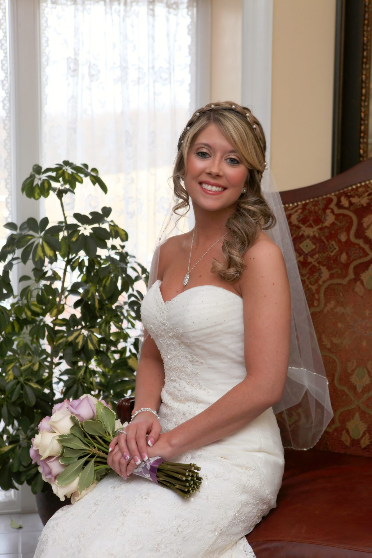 Bride sitting on leather couch by window in bride's room before wedding ceremony