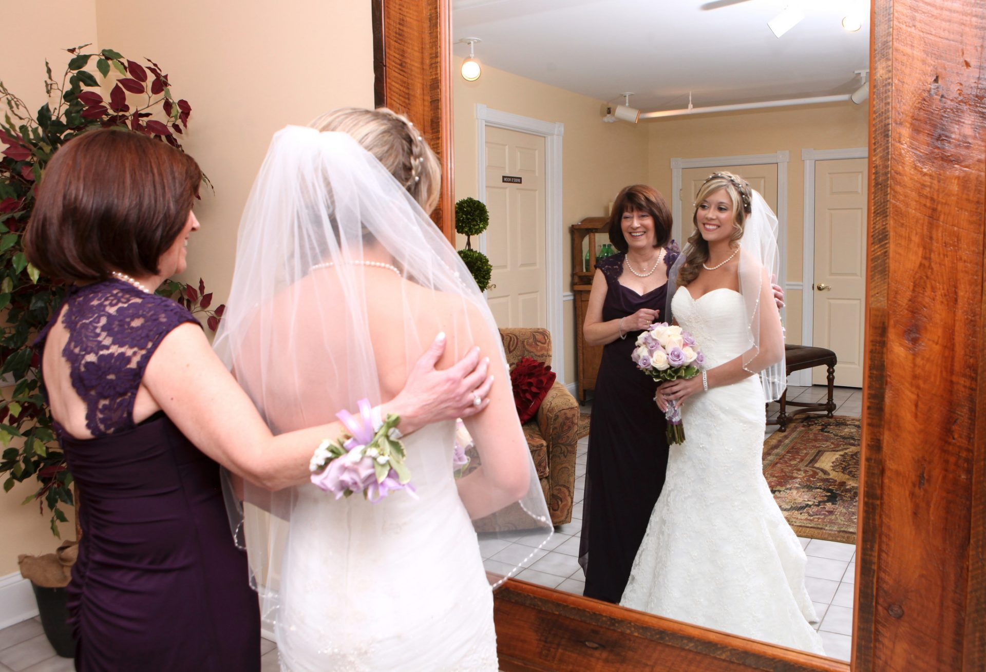 Bride and mother of bride embrace in front of large mirror in the bride's room