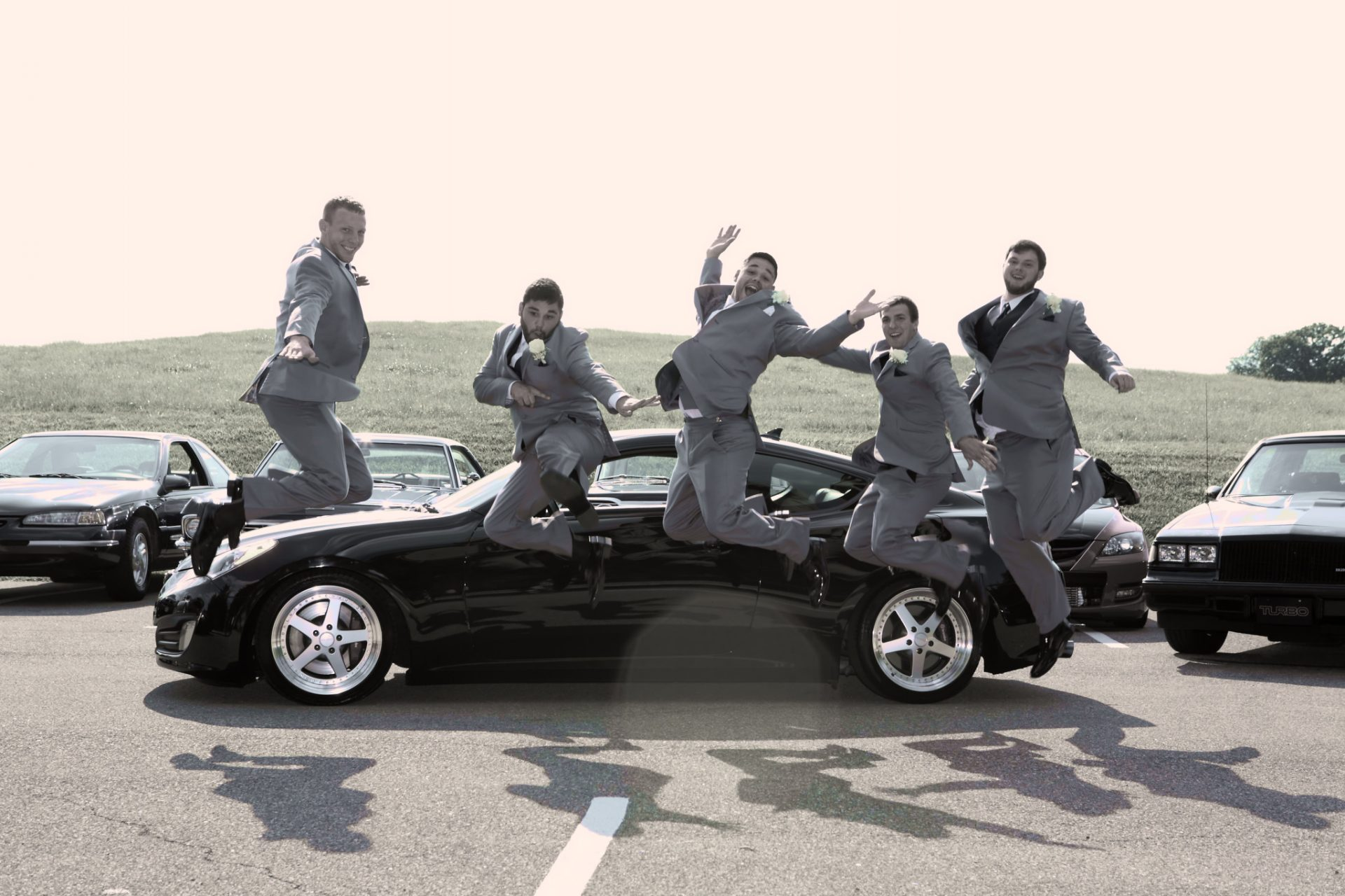 groomsmen jumping by car in parking lot