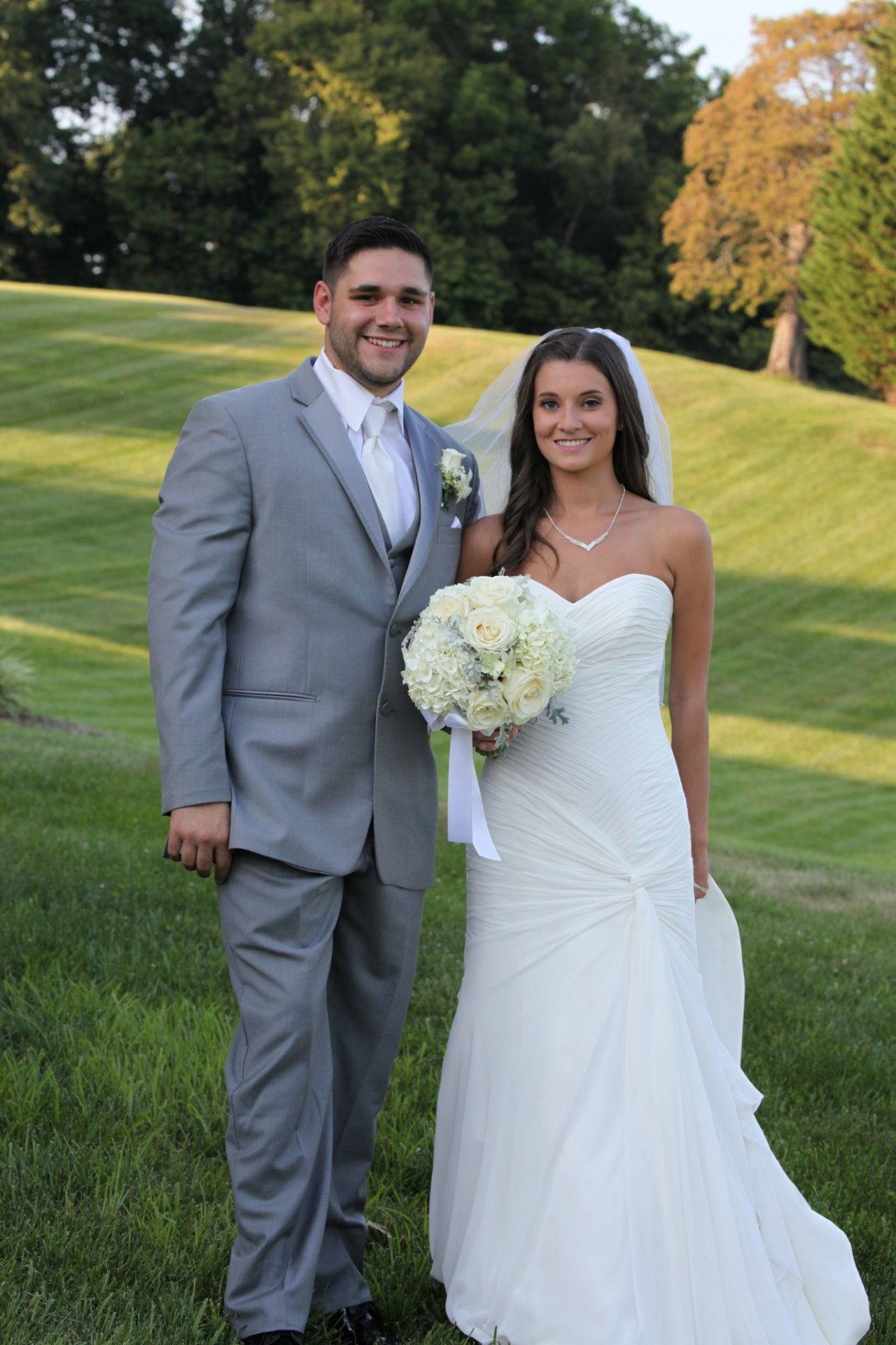 Bride and groom pose by ponds on the expansive grounds of Morningside Inn