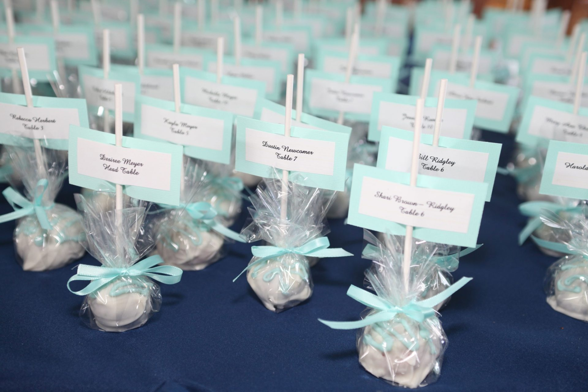 Cake pop party favors wrapped in plastic with teal bow also used as table assignments