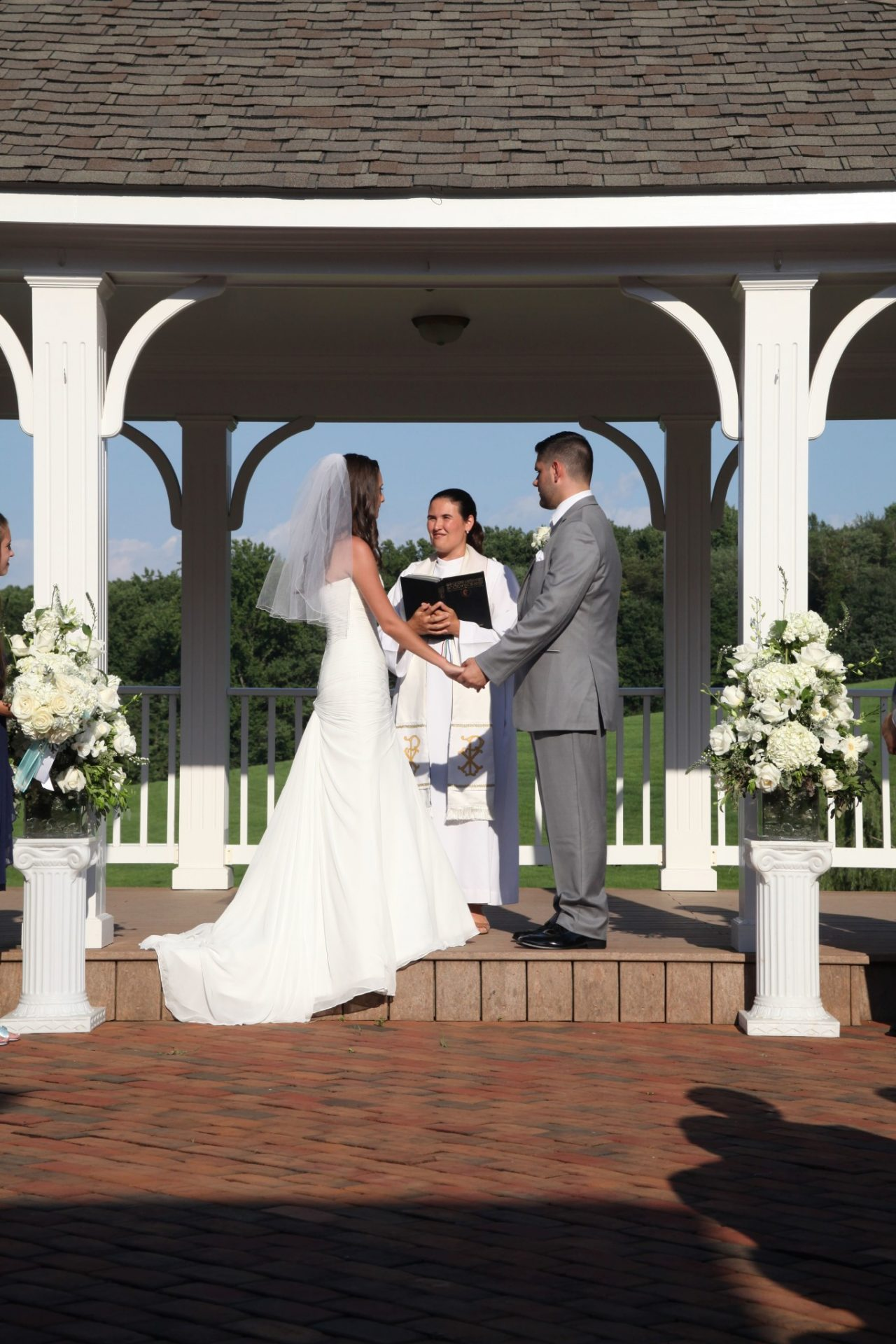 Close up of bride and groom on pavilion during outdoor wedding ceremony