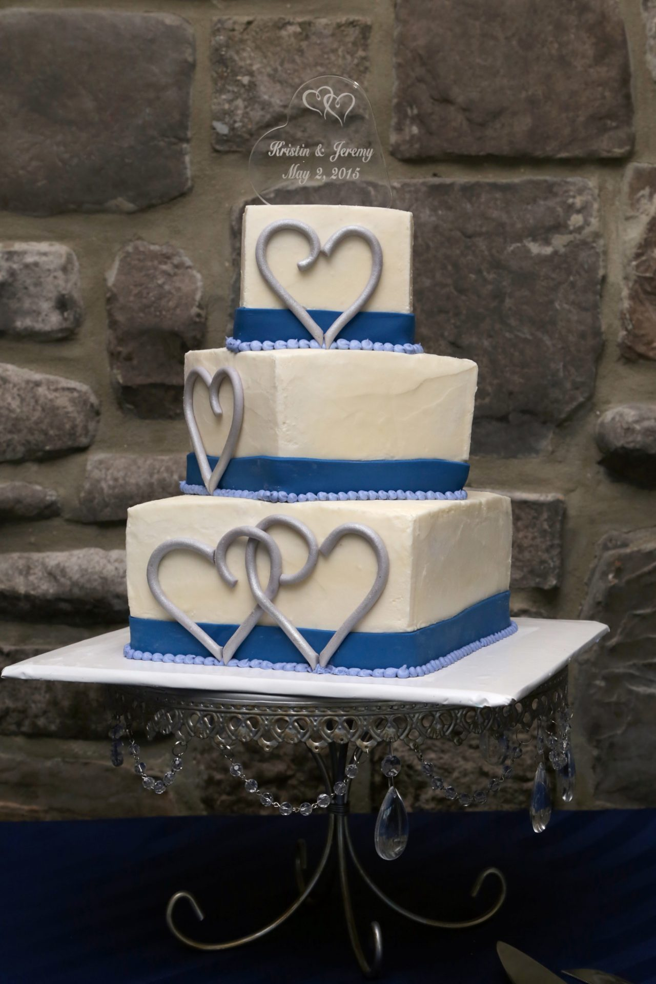Jeremy and Kristin's cream and blue wedding cake with silver hearts drawn in icing on the sides of three tiered cake