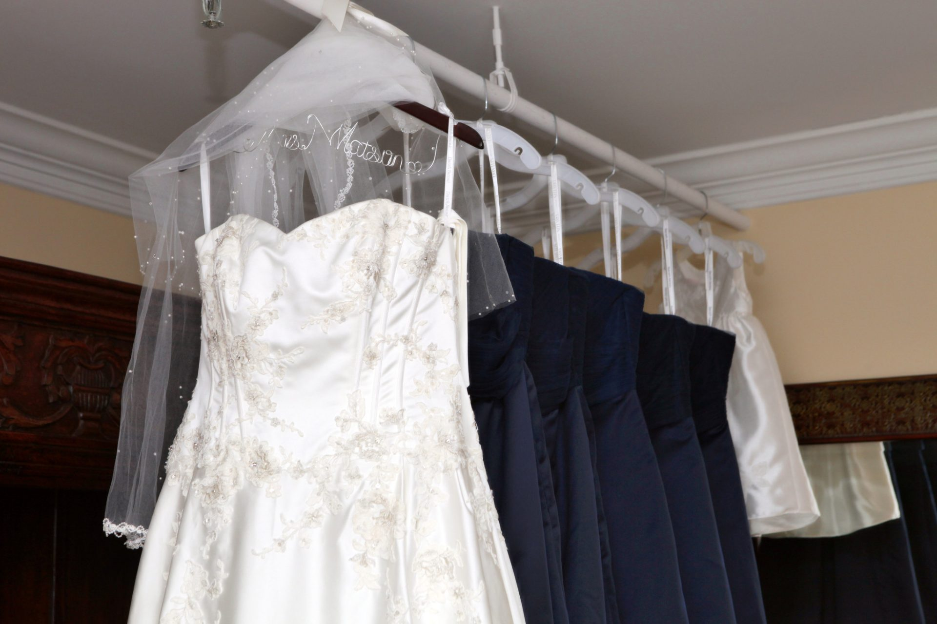 wedding dress and brides' maid dresses all hanging in brides room at morningside inn for this may outdoor wedding
