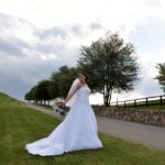 bride in the grass by the stone wall