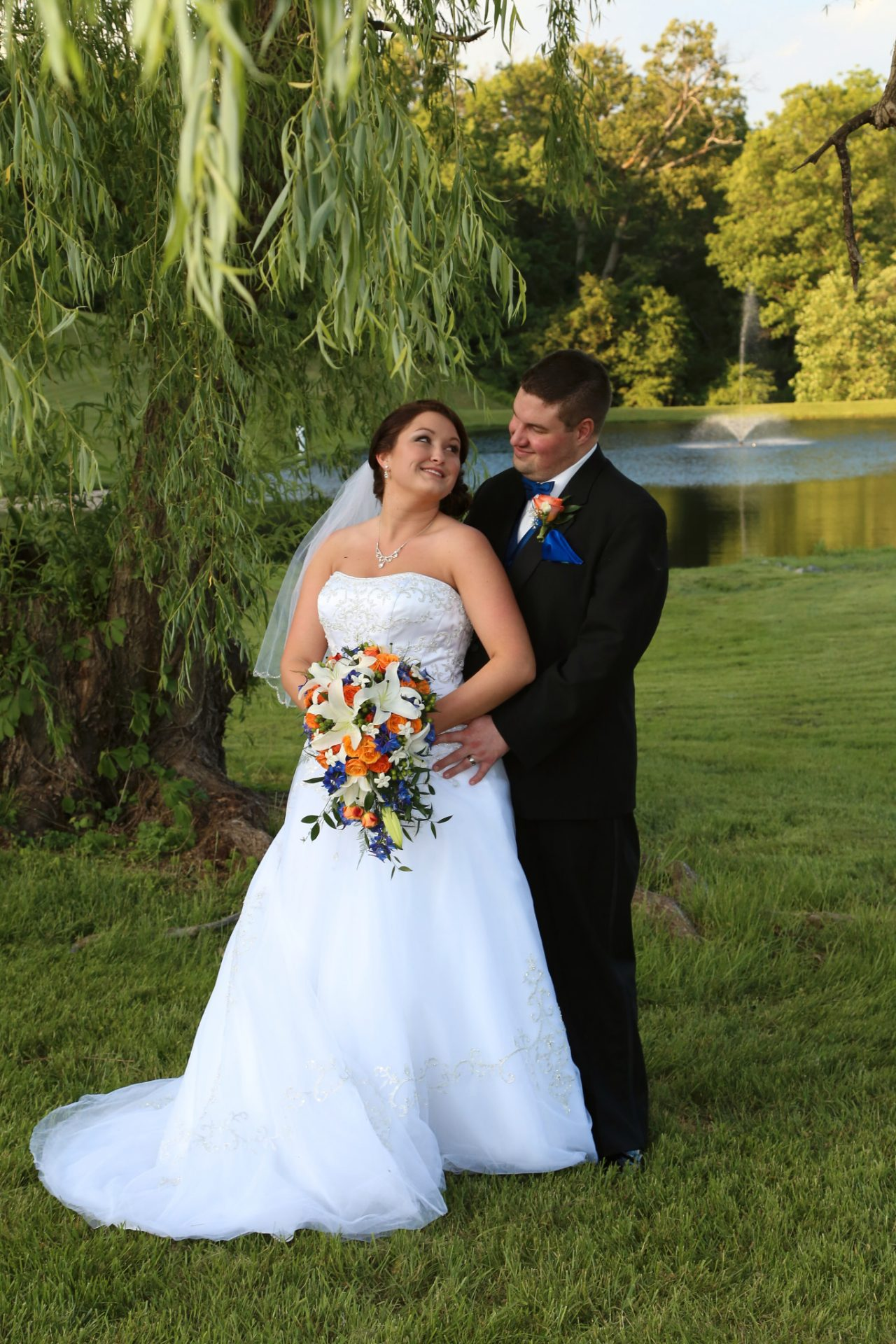 bride and broom pose in front of the old willow tree at morningside inn