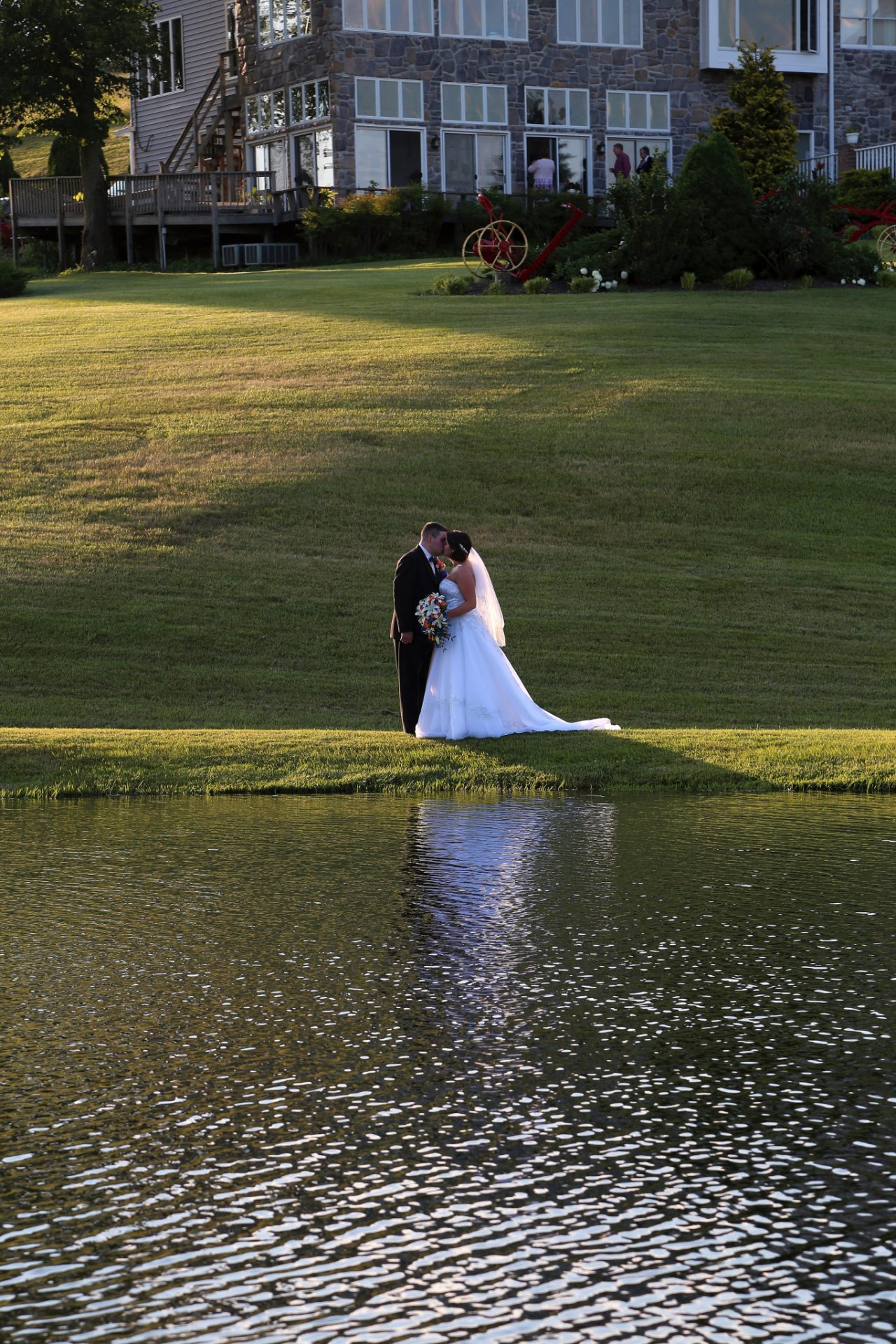 bride and groom pose for photos in front of the pond wedding