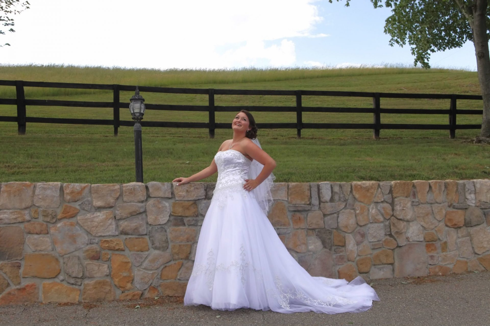 bride posing in front of the stone wall