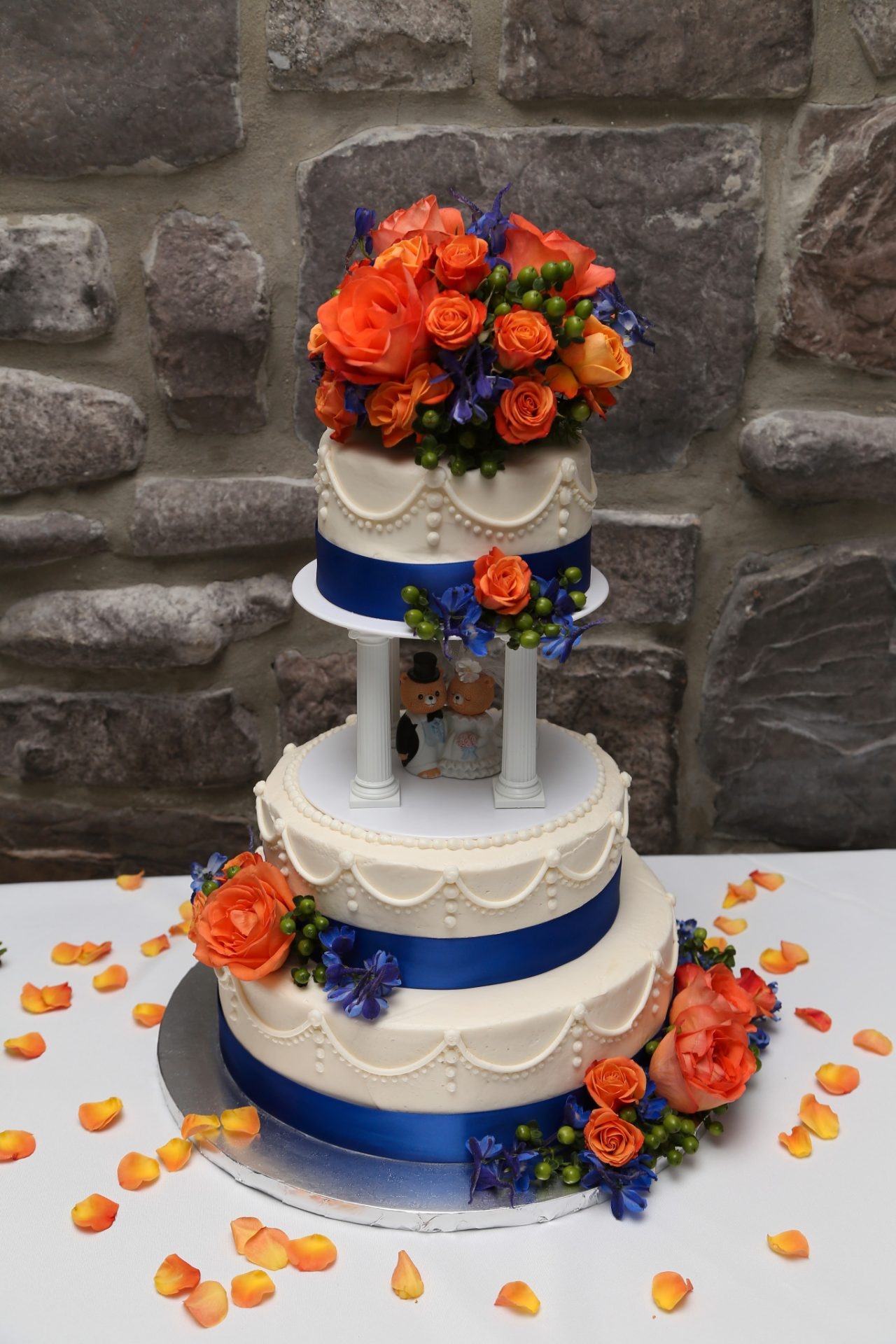 wedding cake with cream icing and pink, orange flowers and blue ribbon