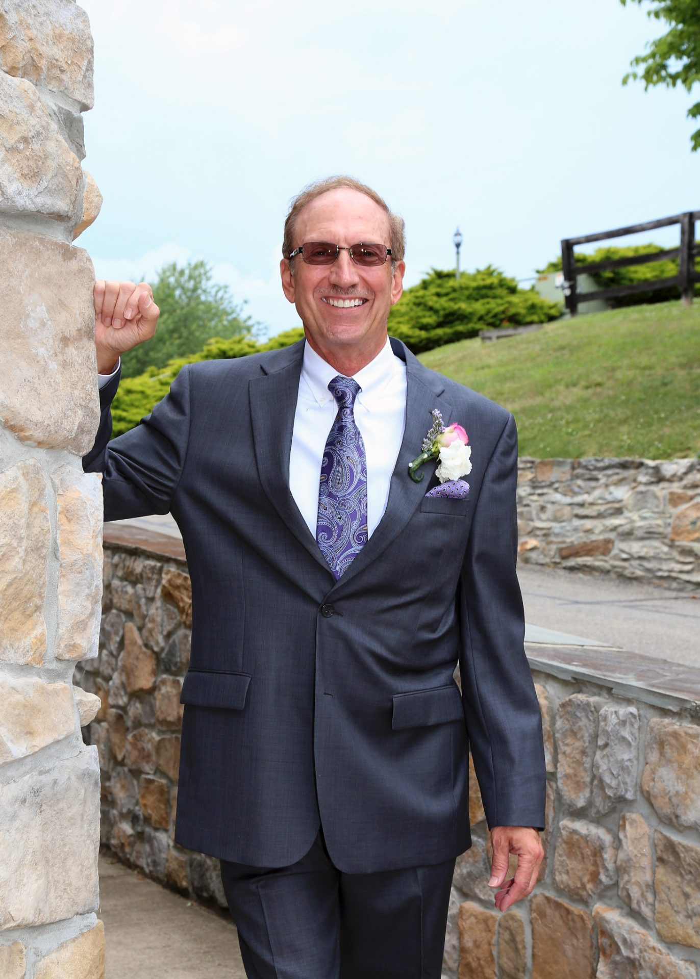 Groom poses by the stone wall in the back of Morningside In before the wedding ceremony on the outdoor pavilion