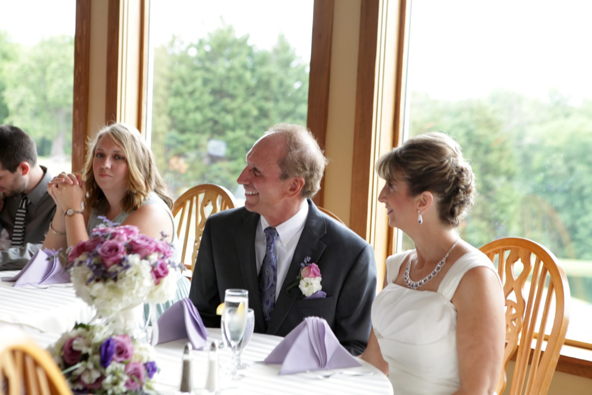 Bride and groom are all smiles during the best man speech as they sit in from of the windows in the main dining room. The dining room is lined with windows for expansive views of the rolling green hills at Morningside Inn.