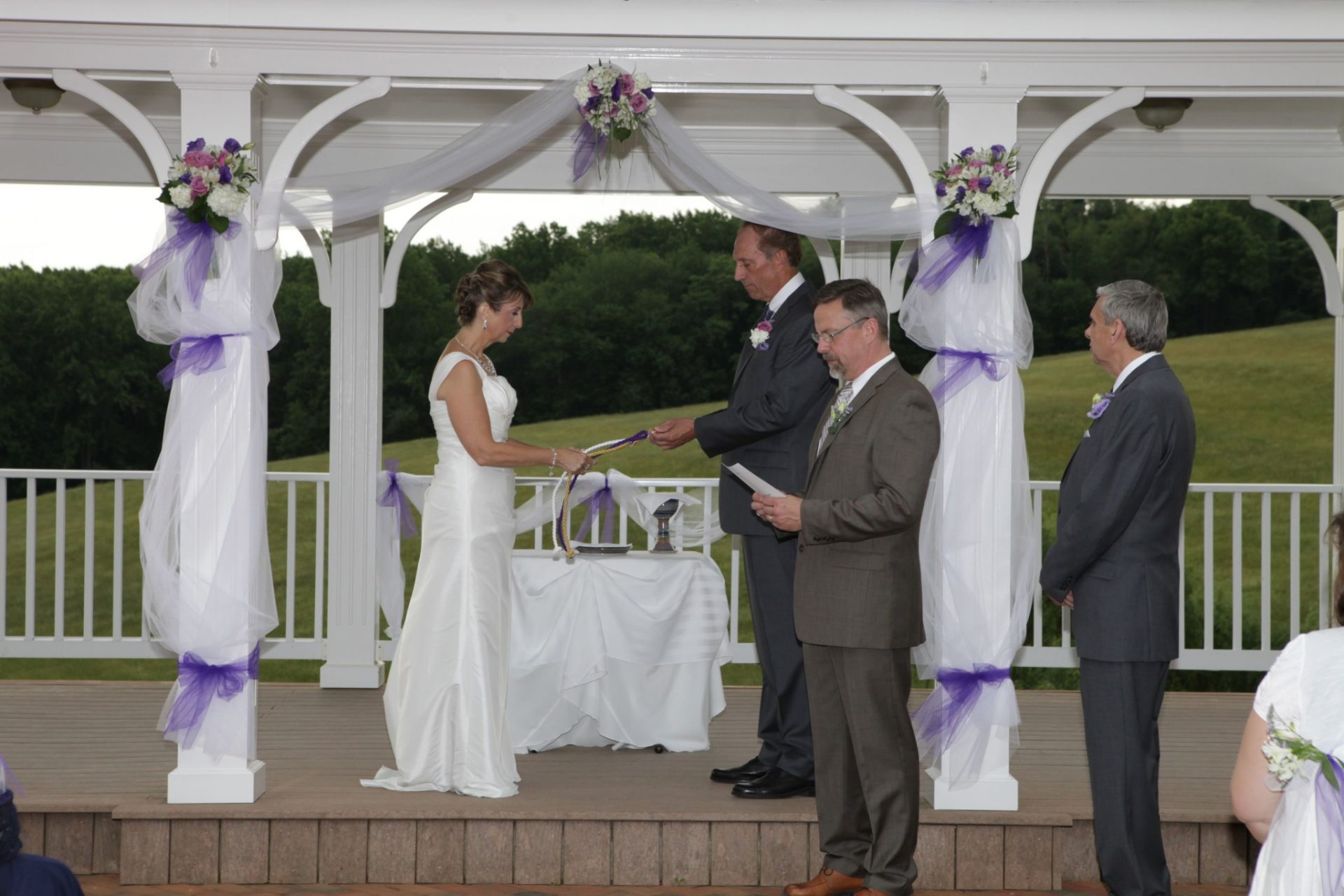 Summer wedding at Morningside Inn on the outdoor pavilion. Bride and groom hold hands on the pavilion decorated with purple and pink flowers and white linen