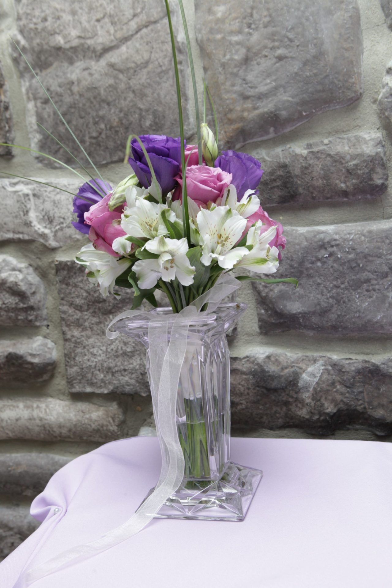 Bride and groom chose pink, purple, and white color scheme as seen in this floral arrangement used as table centerpiece.