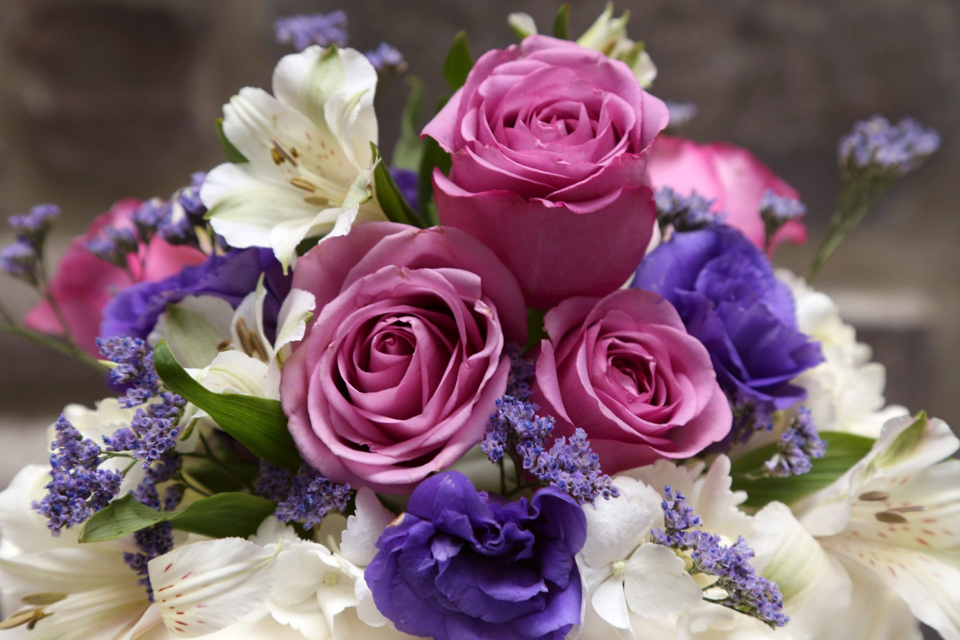 Close up of pink and purple roses used in summer wedding floral arrangement.