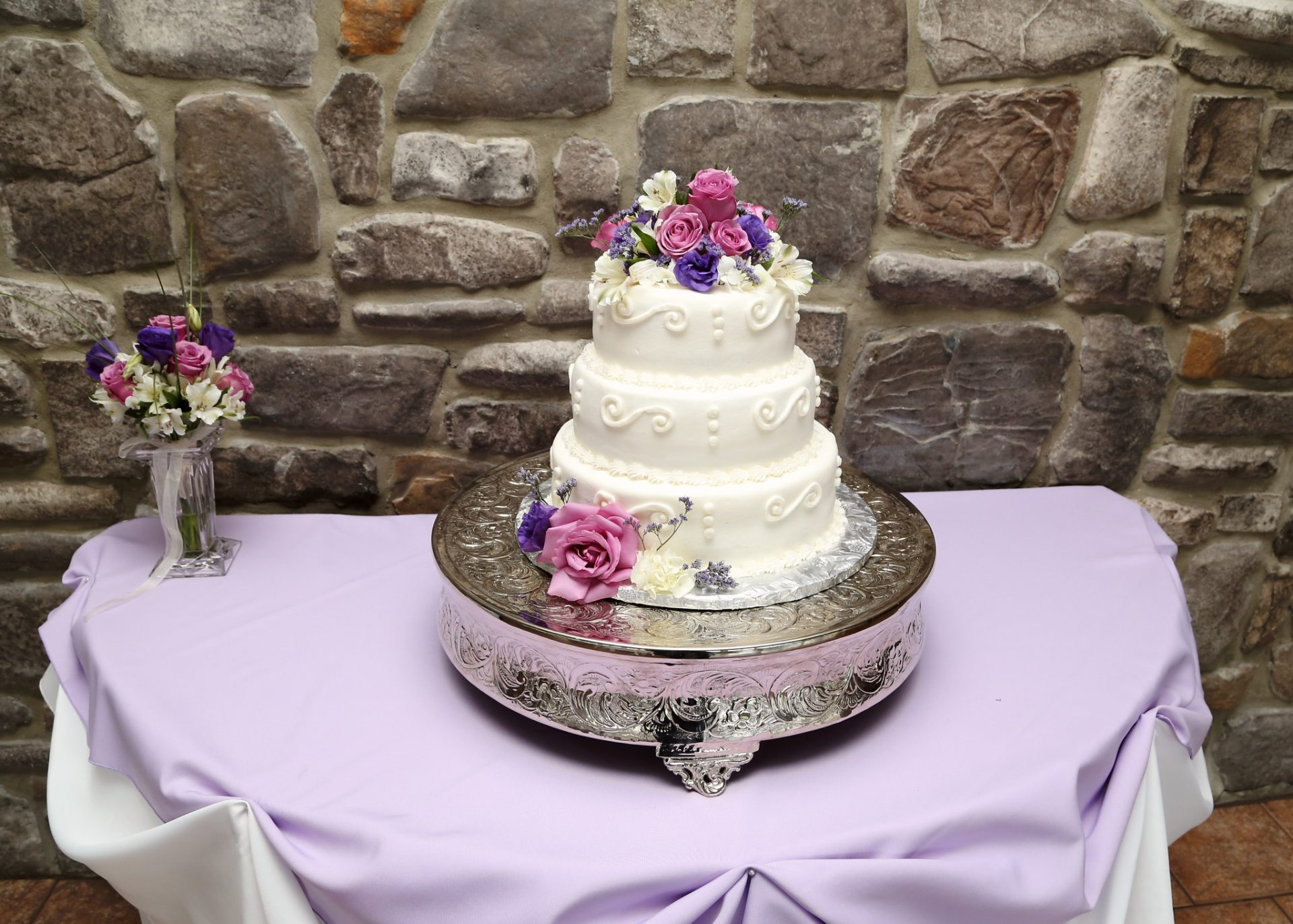 Three tiered wedding cake with white cream icing and decorated with pink and purple flowers. The cake sits on a silver cake display stand.