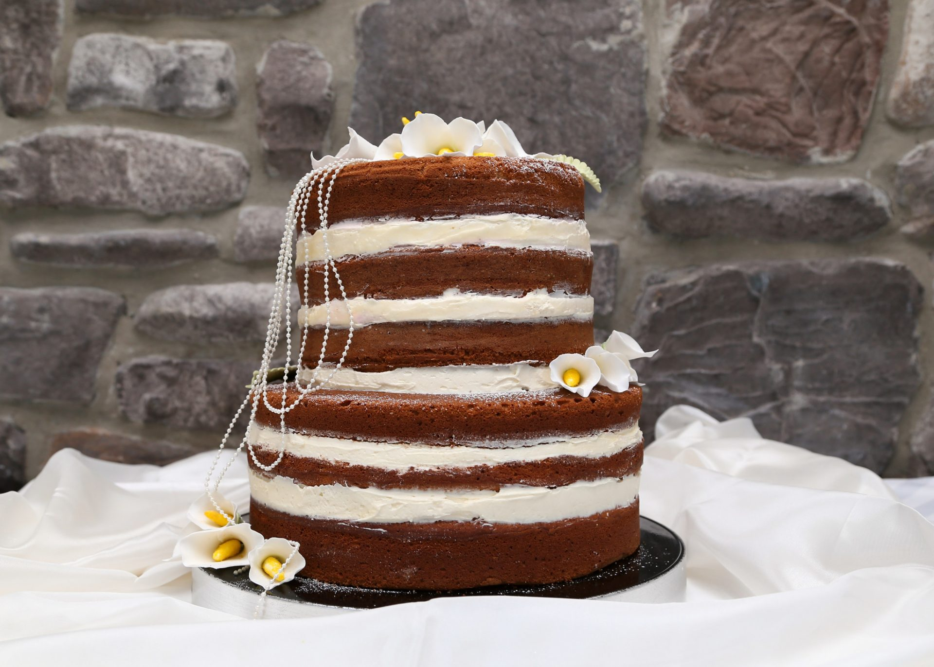 Naked wedding cake topped with flowers