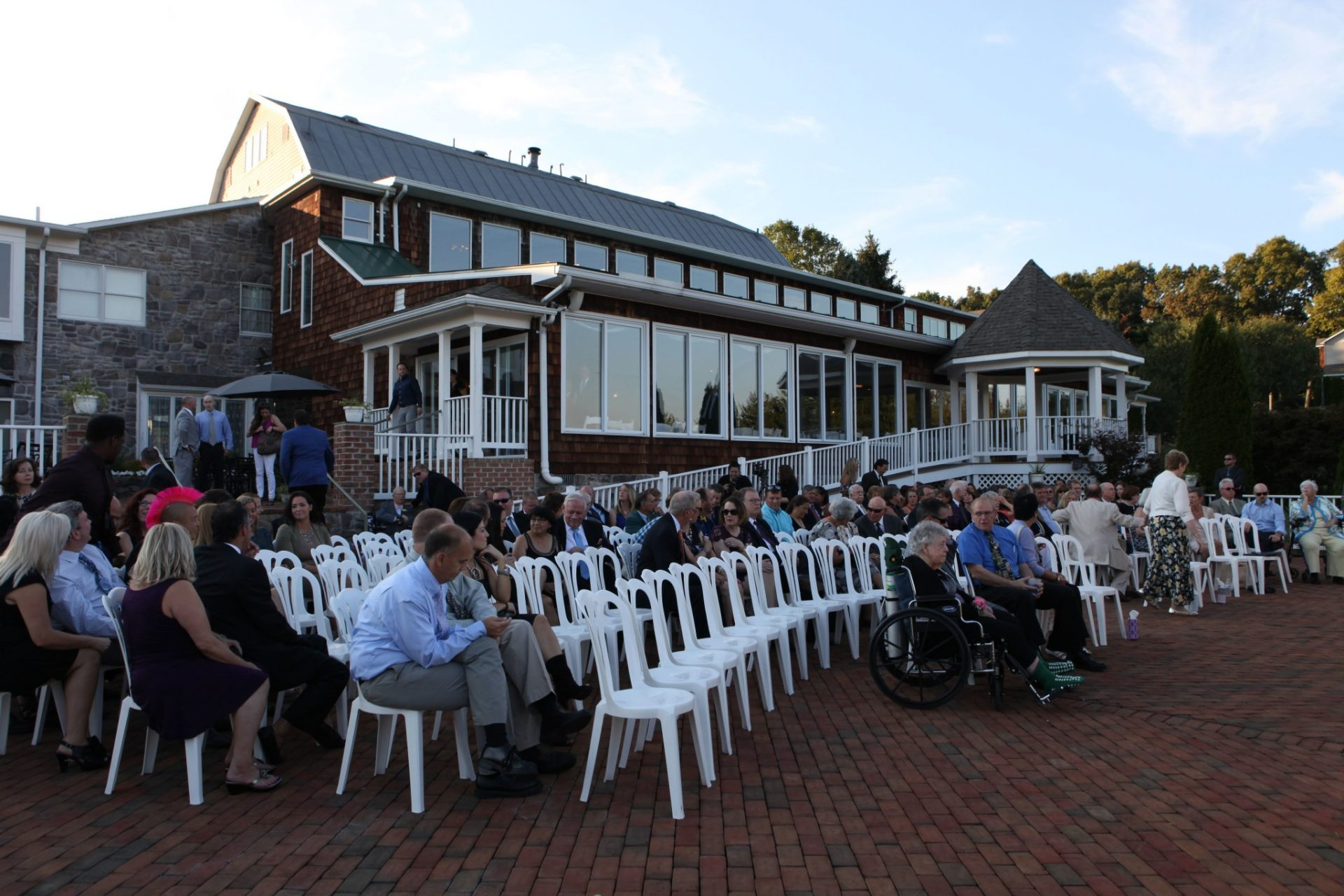 Guests prepare for wedding by taking their seats on the brick patio before wedding
