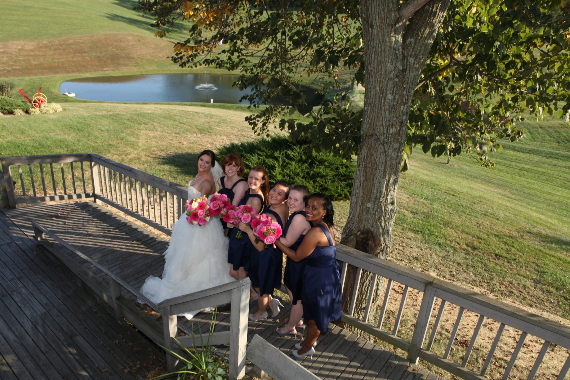 bride and bride's maids pose on deck that leads to the brick patio and wedding pavilion