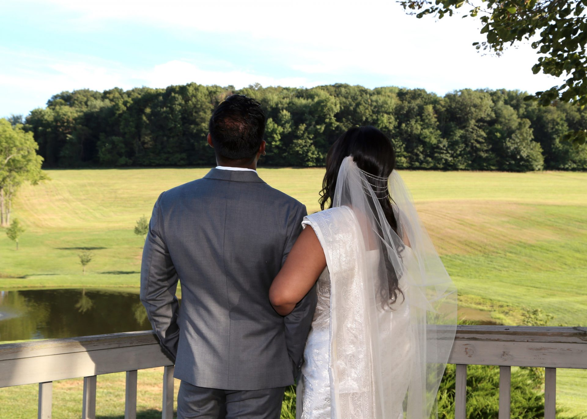Bride and Groom enjoy view on deck leading to large brick patio