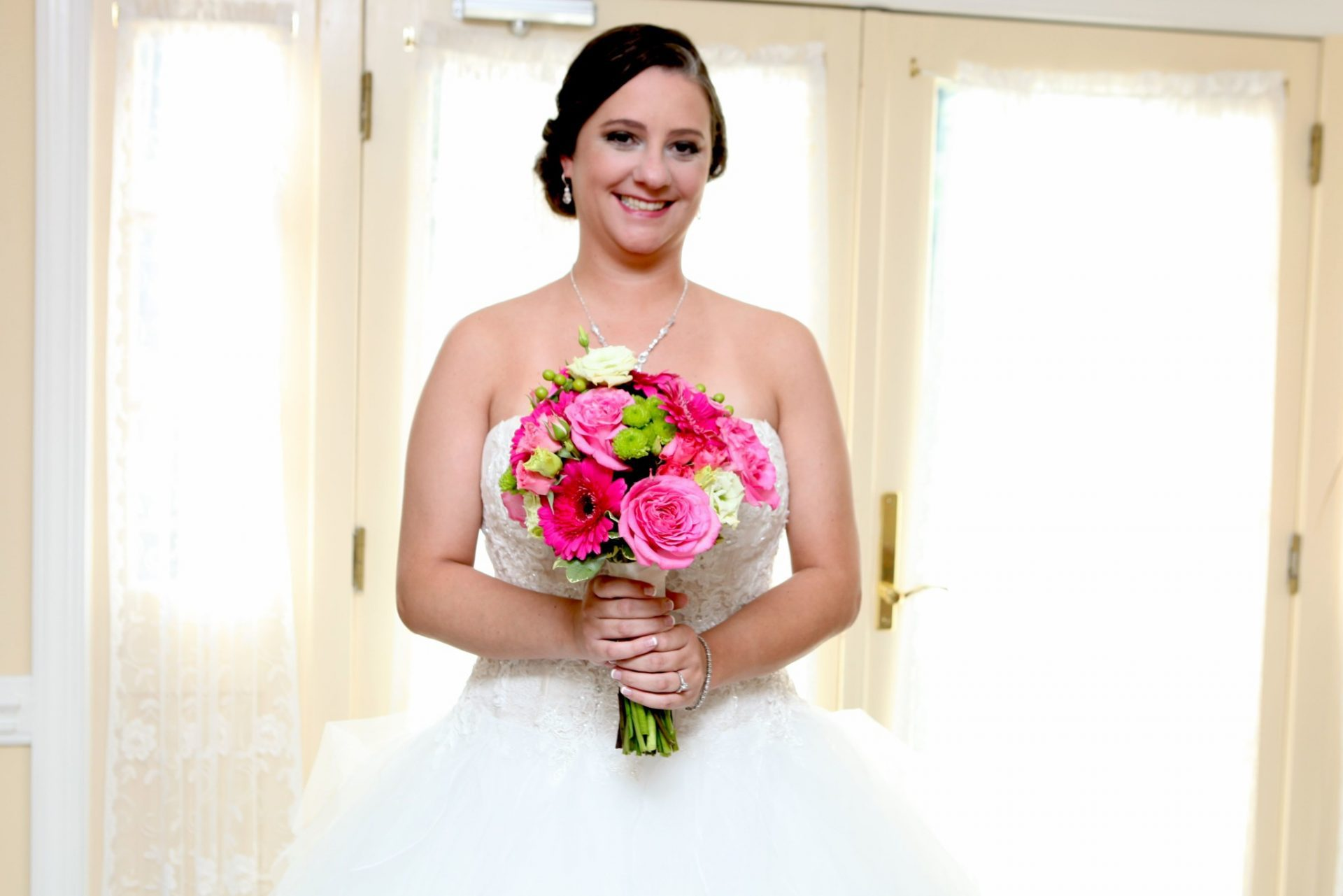 Bride poses by window in bride's room