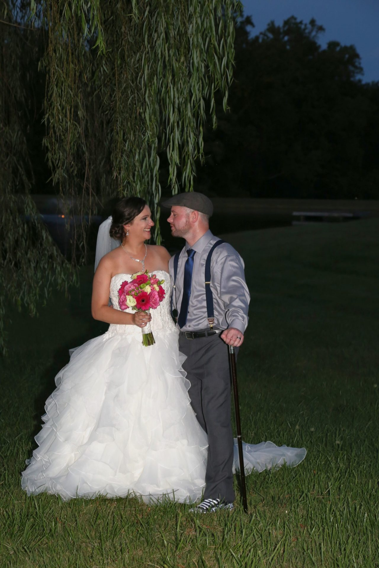 Bride and groom pose by old willow tree by pond.