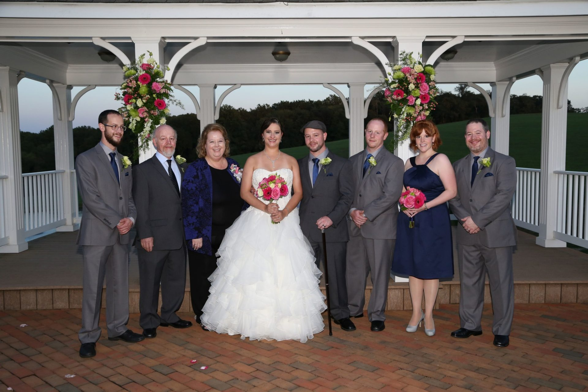 Wedding party on brick patio in front of wedding pavilion