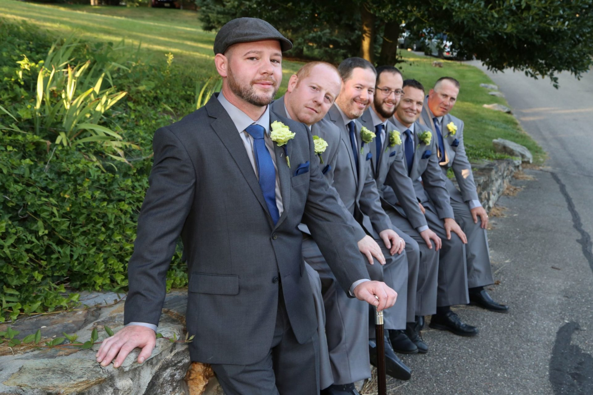 Groom and groom's men line up on stone wall outside of groom's room