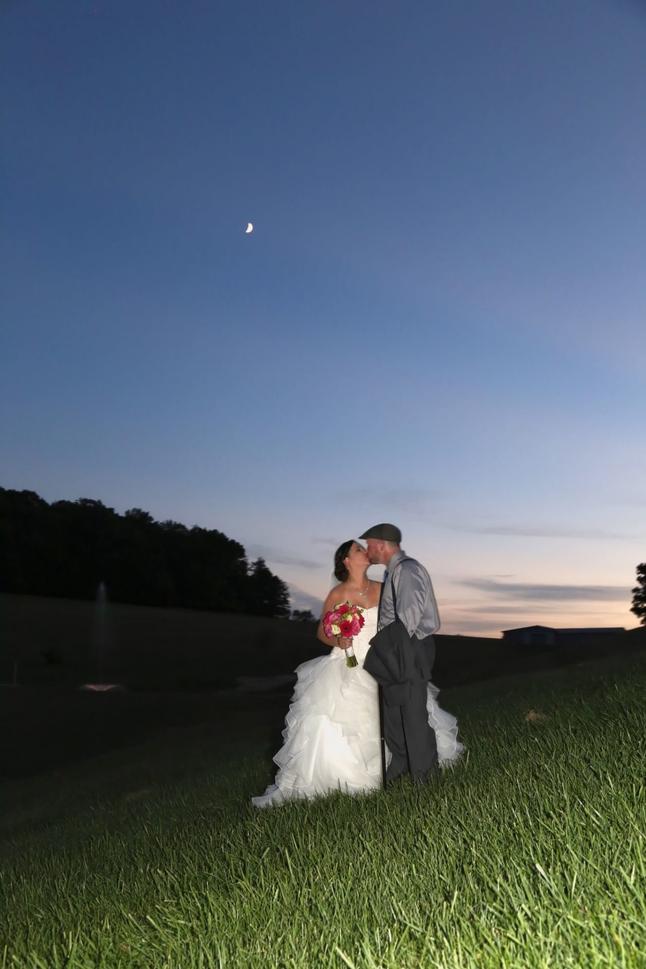 Bride and groom kiss as sunsets after gorgeous maryland wedding