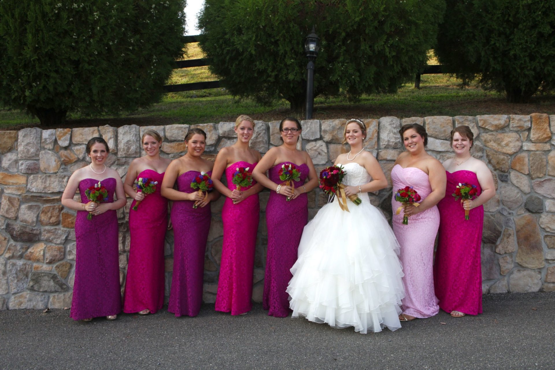 Bridal party poses by stone wall in front of Morningside Inn wedding venue in Frederick MD