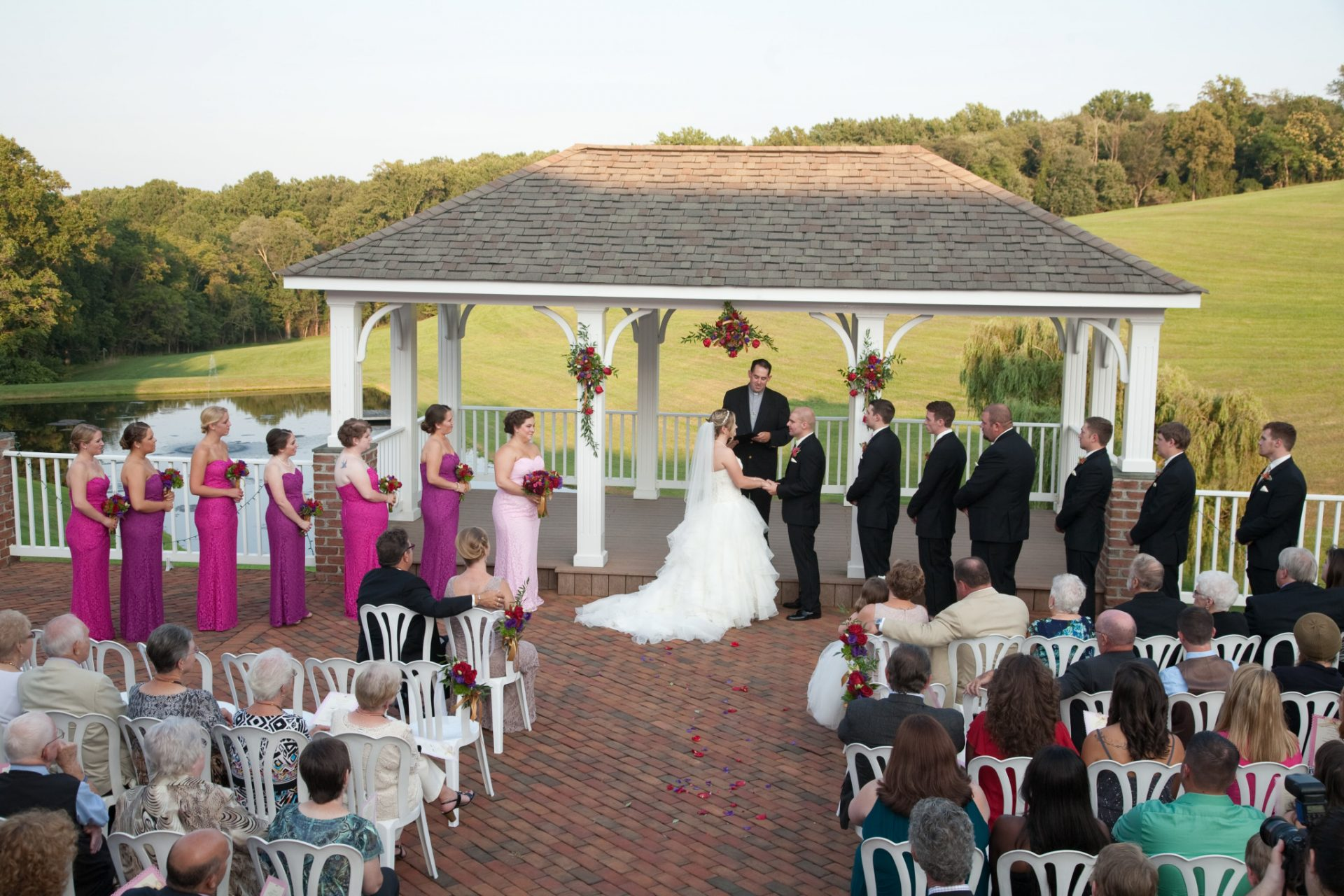 Bride and Groom exchange vows on pavilion during outdoor wedding ceremony