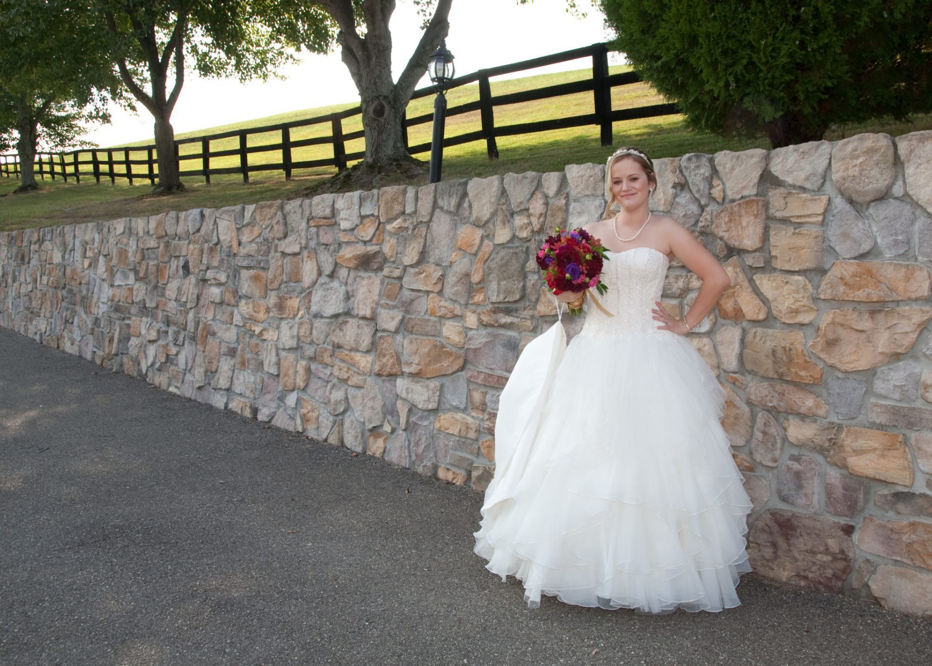 Bride poses by old stone wall at Morningside Inn wedding venue