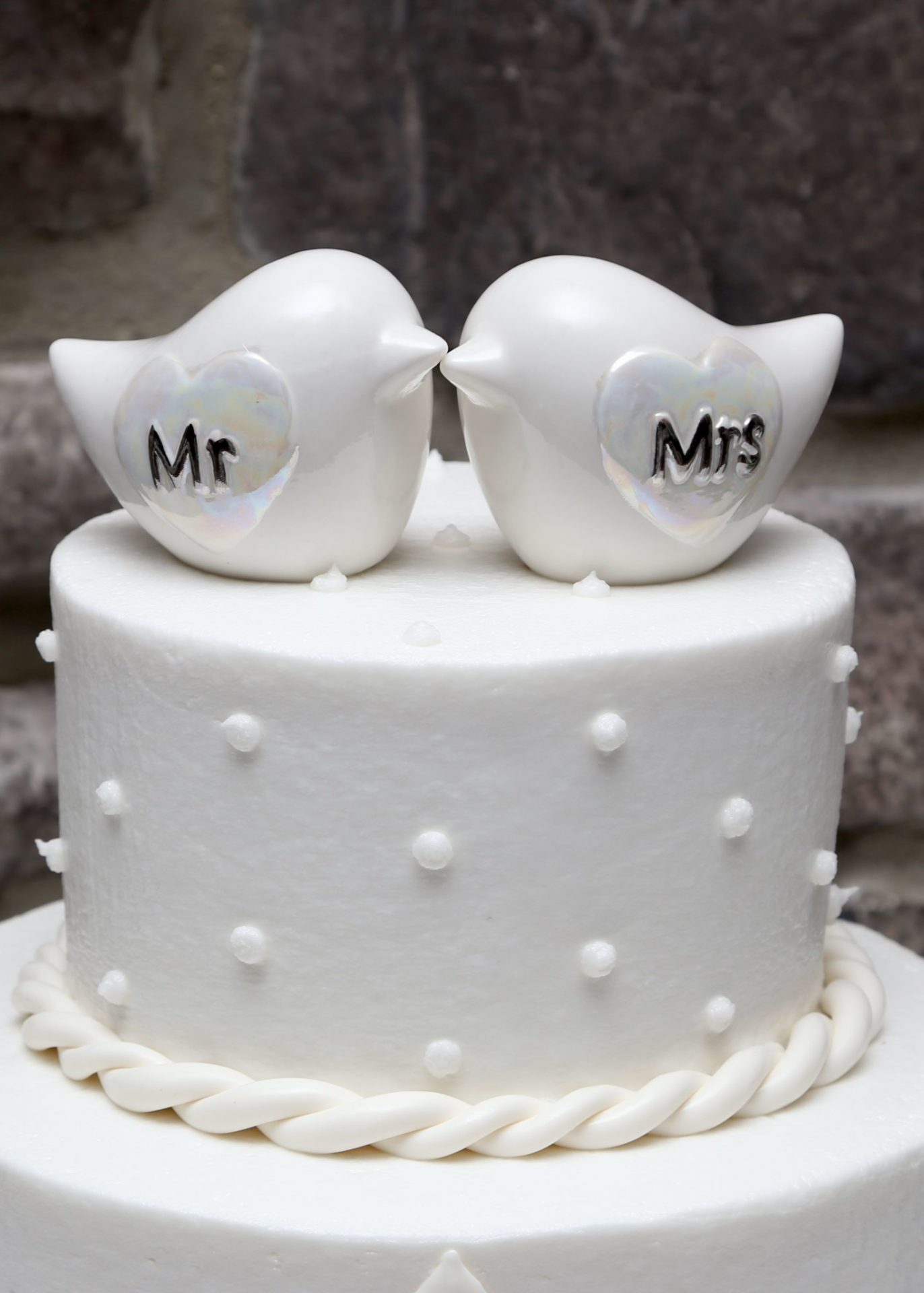 Wedding cake is topped with two white doves labeled with MR andMRS