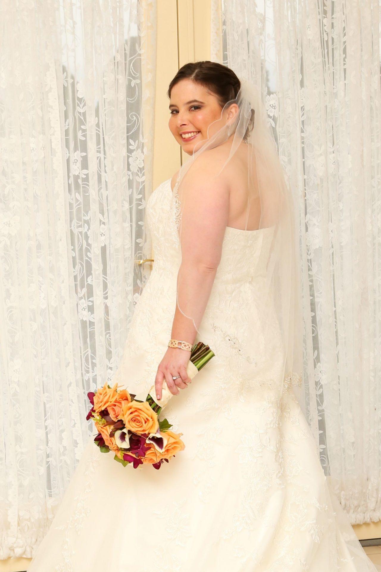 Bride standing by door in bride's room before her fall wedding in Maryland